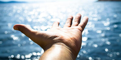 outstretched hand with water in the background, Narrowing Your Focus: The Key to Being a Successful Developer